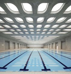 Zaha Hadid designed the London Aquatics Center for the 2012 summer Olympics. It's undulating concrete roof features cutouts that allow natural light to filter in across the pool's blue water.