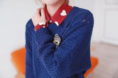 Very cute layered look with the blue sweater over the red heart patterned shirt.