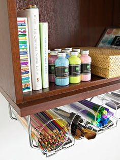 ORGANIZE WITH A WINE RACK.  Attaching under the shelf wine or stemware racks to a wall bookshelf, gives you more room for those everyday supplies. Simply insert glass cylinders in the racks then fill with pens, pencils, markers, and even paint brushes.
