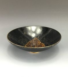 """FINE Chinese JIZHOU Ware Tea Bowl. The simple shallow bowl shape, raised on narrow foot ring, the interior decorated with a naturalistic leaf decoration. The glaze is of a dark brownish olive tone streaking to a creamy coffee brown simulating tixi lacquer and stopping above the concave base exposing the pale buff foot rim. 2"""" H x 5-7/8"""" D"""