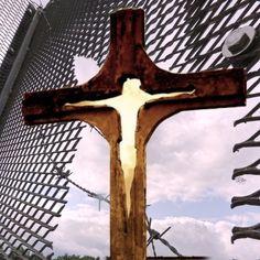 """Mein Kreuz-Weg  Ich möchte Euch einladen, mir auf einem Kreuz-Weg zu folgen. Nein, es ist kein Kreuzweg, sondern ein Weg der Kreuz. Das Wesentliche an diesem Bild ist das Loch im Zaun. Aus diesem wächst ein Kreuz. In diesem Kreuz befindet sich schließlich eine """"Jesusfigur"""". Ich weiß nicht, ob es Jesus ist. Es ist eine Person, das Bild einer Person. Ich habe diese Figur in die Unschärfe abgleiten lassen. Für mich stellt dieses Bild die Überwindung der Grenze dar. Ein Schimmer von Hoffnung. Fence, Figurine, Art, Photo Illustration"""