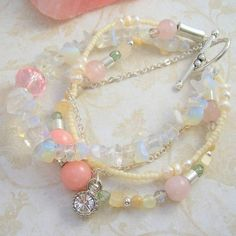 """Lokahi by AURAGEMSbyHeather, $62.75. Four different strands intertwine to make this lovely, romantic pastel semiprecious gemstone bracelet: silver, opal, freshwater pearls, rose quartz, faceted crystals, new jade, yellow jade, mother-of-pearl and pink jade. This piece has been named """"Lokahi"""", which is Hawaiian for """"unity""""."""