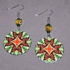 Dangle earrings adorned with my monarch butterfly boho chic mandala new age sacred geometry hippie kaleidoscope design titled Free Spirit. <br /> <br />These lightweight, dainty silver earrings begin with a dangle of dark moss green bicone Swarovski crystal bead and yellow butterfly Swarovski bead that accentuate the colors in the mandala charm that has scalloped edges...