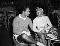 Original caption:Ginger Rogers caught in a hand-holding moment with her new heart interest Jacques Bergerac, youthful French actor, after completion of tennis play at the Racquet Club here. The twosome were tennis partners in weekend tournament play here at the club. November 20, 1952