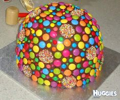 Chocolate shell decorated with smarties and chocolate freckles encasing a chocolate cake inside with loose lollies on top which spill out when cake is smashed with toy hammer.