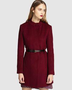 Abrigo largo en color burdeos, de manga larga y cuello cerrado. Tiene cierre delantero oculto, dos bolsillos laterales, trabillas en la cintura y cinturón de piel.