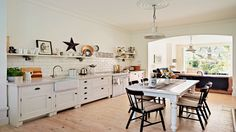A shelf running the full length of this open-plan kitchen-diner is used to add character and personality, with a display of photos, ornaments and pretty kitchenware