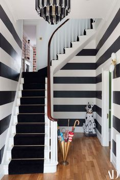 """When I told people I was going to paint my entranceway black and white stripes, everyone thought I was insane. But I'm excited by that kind of high contrast."" #paint #stairs #statue #umbrellas #brass #chandelier #stripes #staircase #banister #runner Black And White Stairs, White Staircase, Black And White Interior, Black And White Design, Striped Hallway, Striped Room, Striped Walls, Architectural Digest, Leather Sleigh Bed"