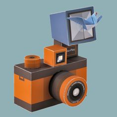 A paper toy shaped like a retro camera made of paper to be built with an origami bird that comes out of the flash. Cardboard Camera, Paper Camera, Paper Crafts Origami, Diy Paper, Paper Art, Origami Bird, Printable Crafts, Printable Paper, Printables