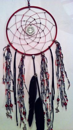 """YIN AND YANG  This handmade dream catcher is approximately 24"""" long from the top of the bail to the tip of the feather. The ring and web are variegated shades of red with silver and iridescent black accent beads and a yin and yang focal in the center. Hanging from the bottom are a mixture of red, silver, black and grey beads with small spikes and dragons, along with leather cording and feathers.  Currently for sale - $75 + shipping $17 (USPS)"""