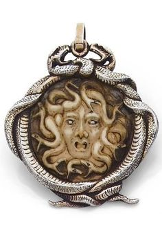 AN ART NOUVEAU IVORY AND SILVER PENDANT, BY RENÉ LALIQUE. Featuring a round, carved and stained ivory representing Medusa, framed by coiled silver snakes. Signed.  #ArtNouveau #Lalique #pendant