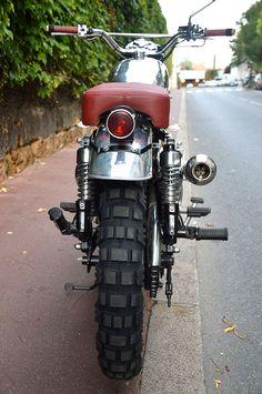 Scrambler, définition : né dans les années 60 aux USA, un scrambler est une moto destinée à arpenter tous les types de routes, y compris les chemins tout-terrains ! Le scrambler est donc doté de po…