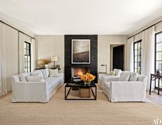 In the living room, a work by Jack Pierson is mounted on a blackened-steel fireplace surround fabricated by La Forge Française; an RH sofa and armchairs, all slipcovered in a Perennials fabric, flank an RH cocktail table.