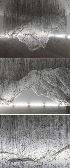 """In his installation, reverse of volume RG, Yasuaki Onishi uses the simplest materials — plastic sheeting and black hot glue — to create a monumental, mountainous form that appears to float in space. The process that he calls """"casting the invisible"""" involves draping the plastic sheeting over stacked cardboard boxes, which are then removed to leave only their impressions. This process of """"reversing"""" sculpture is Onishi's meditation on the nature of the negative space, or void, left behind."""