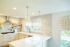 A kitchen in suburban Detroit uses modern slab-style cabinets with traditional touches to achieve a very inviting and warm feel. Kitchen Slab, Kitchen Shelves, Kitchen And Bath, New Kitchen, Kitchen Design, Brass Kitchen, 1960s Kitchen, Mid Century Modern Kitchen, Young House Love