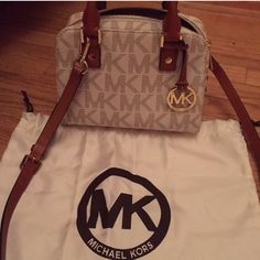 """NEW Michael Kors Small Satchel FLASH SALE 100% Authentic MK Monogrammed satchel in Vanilla and Luggage Leather Trim. New without tags. In beautifully perfect condition!! Selling because I need room for others Measurements 8.5"""" wide x 6"""" high x 3.75 bottom. Comes with dust bag! Top zip closure. Leather handle. Crossbody strap included (adjustable and detachable) with 22"""" drop MK fabric inside lining with one super wide and convenient leather-trimmed pocket with gold MK leather plaque. Gold…"""