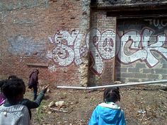 students analyzing graff in a garden lot with an abandoned building