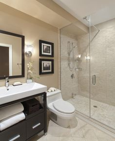 Sharp looking bathroom.  Looks like a swanky hotel.  You can never go wrong with travertine tiles.  Like the low profile toilet and vanity cabinet style.