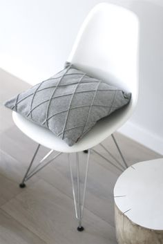 pale grey diamond pintucked cushion (pillow) against white and pale grey wood floors