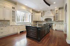 Esta cocina tiene un amplio espacio abierto dominado por una isla de color negro, en contraste con los gabinetes blanco circundante.