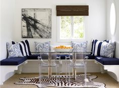 blue and white breakfast nook with pop of orange, lucite chairs