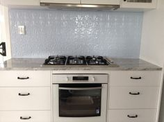 Pressed tin used on kitchen splashback.  For more details on this design see: http://www.heritageceilings.com.au/tempat/petra.php