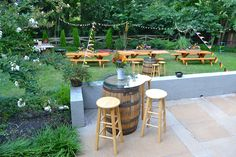Casual Backyard Biergarten Engagement Party: Picnic tables & whiskey barrel bistro table with pub stools & flowers