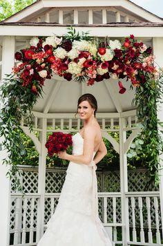 Stunning bride under a beautiful floral arbor #bride #bridal #floralarbor #redwedding #romantic