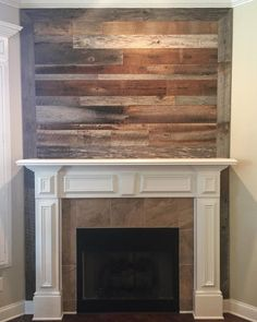 White fireplace in front of the barn board wall in the media room