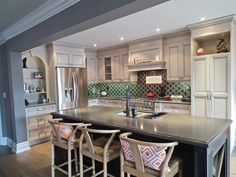 Pops of color and a Piatra Grey countertop make this french provincial style kitchen by Bayview Kitchen Design true eye candy. No wonder why they're living 'la dolce vita'!