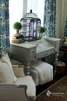 A painted and distressed antique desk becomes a centerpiece when decorated with old books and a birdcage  (via Living Room Desk Before & After)
