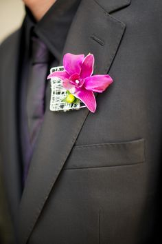 Extremely modern and unique boutonniere featuring a woven silver wire square with one fuchsia orchid bloom.