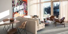 a living room with large picture windows and a large brightly colored painting and an L-shaped sofa