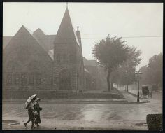 Crossing the street in the rain, ca. 1915