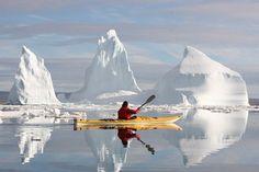 Nunavut, Canada - lone kayaker in water with iceberg & blue skies