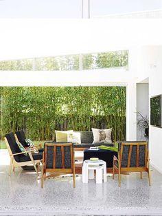 terrasse moderne aménagée avec un salon de jardin en bois et un brise-vue bambou