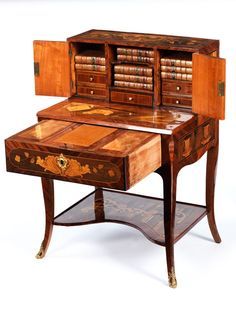 Day Happiness Elegantly curved legs with Bronzeabots. The little table with a wide drawer marquetry of petal and rocaille, fully veneered. The da-over plate located with the representation of letters, pens and writing materials. The essay with a central drawer and two side compartments, this brand benefits with birds in large rococo cartouches. In the middle of a letter tray, palms up well decorated with marquetry, cartridges, rocaille, C-scrolls, flowers and foliage.