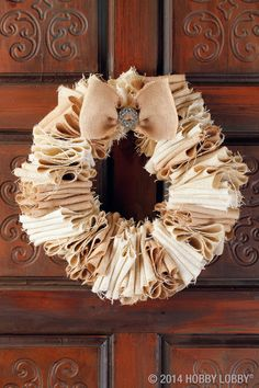 This two-toned wreath equals full circle style with layer upon layer of both bleached and natural burlap. The base is a recycled coat hanger, untwisted at the neck. Each strip of fabric is accordion-folded and then stacked onto the wire. When we reached the desired fullness, we shaped the wire into a wreath and secured the shape by wrapping jute around the ends. It may be helpful to reinforce both folds and closure with hot glue.