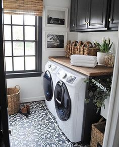 Black/White/Wood - Laundry room with black and white cement tiles, wood countertop, black window, wooden wood blinds, and black cabinets plus some greenery. Who wouldn't want to fold laundry in there!
