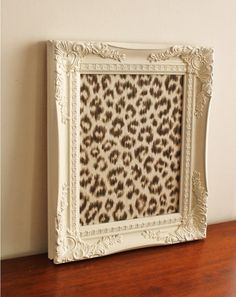 Bulletin board with white painted wooden frame and snow leopard fabric