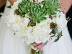 'Shirley Temple'  peonies , green succulents,  scabiosa  pods, white 'Mikado' spray roses, seeded eucalyptus and white  lisianthus  are pulled together with a charming burlap-wrapped handle.   Floral design by  Kio Kreations . Photo by  Gina + Tony Photographers .