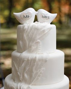 Adorably crafted, this charming porcelain love bird wedding cake topper features pearlized heart designs written with the words Mr and Mrs in silver.