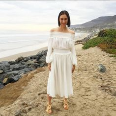 Eva Chen is wearing an off the shoulder white midi dress and gold sandals.