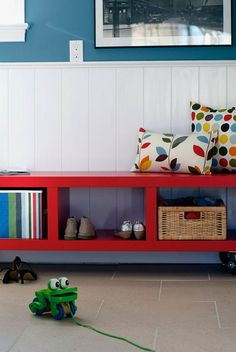 Simple built-in hall bench, so useful with partitions for baskets, shoes, love the bold color & simple lines, especially against the wainscoting. And colorful pillows!