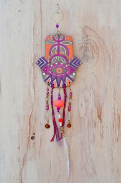 "A hamsa is an amulet shaped like a hand, with three extended fingers in the middle and a curved thumb or pinky finger on either side. It is thought to protect against the ""evil eye."" 