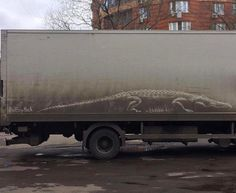 Alligator drawn into dirt on side of a truck.