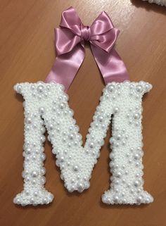 -Letra inicial do nome do bebê em mdf branca  -Com aplique de pérolas  -Com laço de cetim para pendurar  -Medida 19 cm de altura