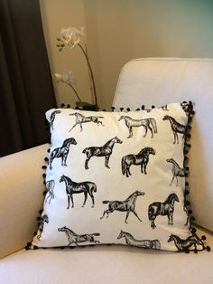 This stylish cushion features a black and white horse print and is finished with black pom poms.  Details: • 100% cotton • Same fabric front and back • Black pom poms • zipper • 45 x 45cm • Cushion cover only  Polyester and feather inserts can be found at IKEA or most craft stores.  Dry-cleaning recommended. Spot clean with damp cloth.