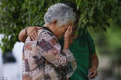 Lesa Mendes, Flores' grandmother, is comforted by Maria Cristina Sepulveda as she views a makeshift memorial set up for the schoolboy at the spot where he died