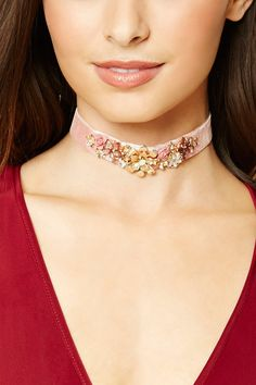 A velvet choker featuring an embellished floral design with faux gems, high-polish ends, and a lobster clasp closure.